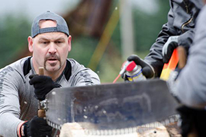 Kensington employee, Dominic Hoy, competes in the Men's Team Hand Bucking event.